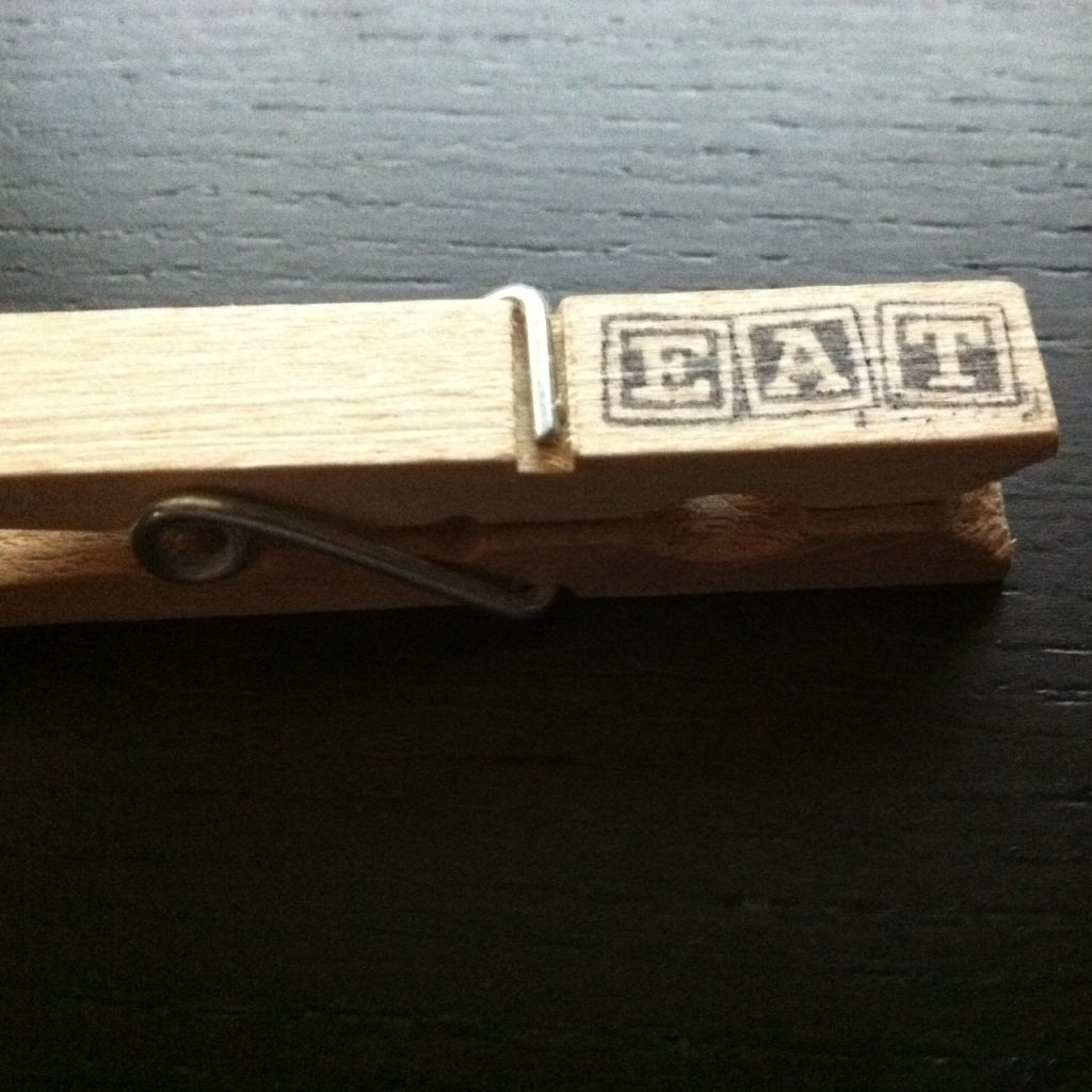 a clothes pin stamped, eat.